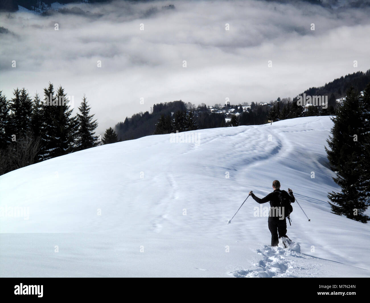 A woman snowshoes below La Bourgeoise overlooking the Giffre Valley and the town of Samoens in the French Alps - Stock Image