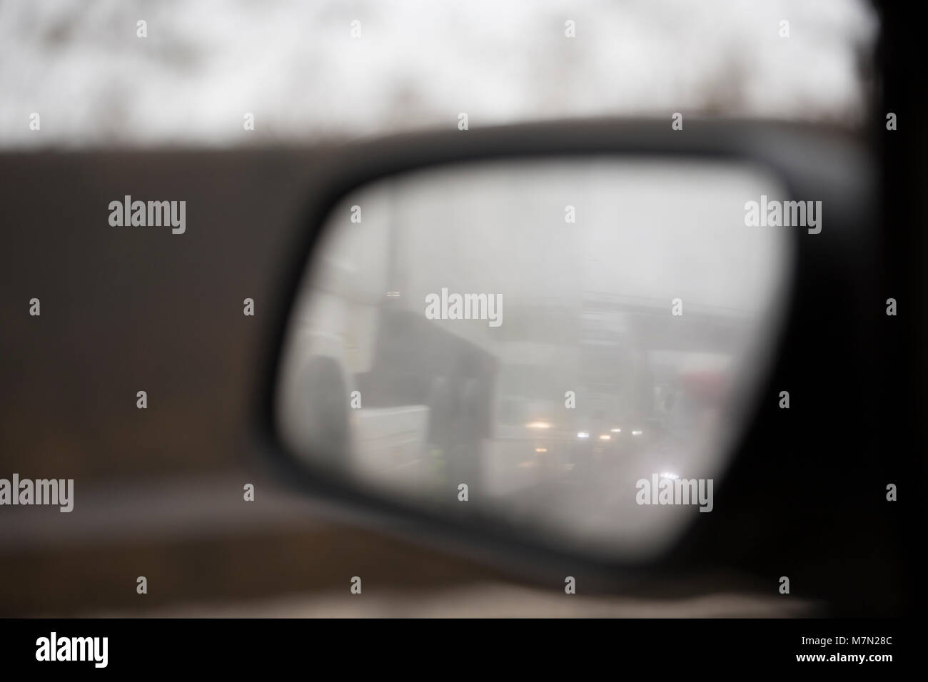 Spray following rain that has covered a nearside wing mirror making rear visibility difficult on a motorway. UK - Stock Image