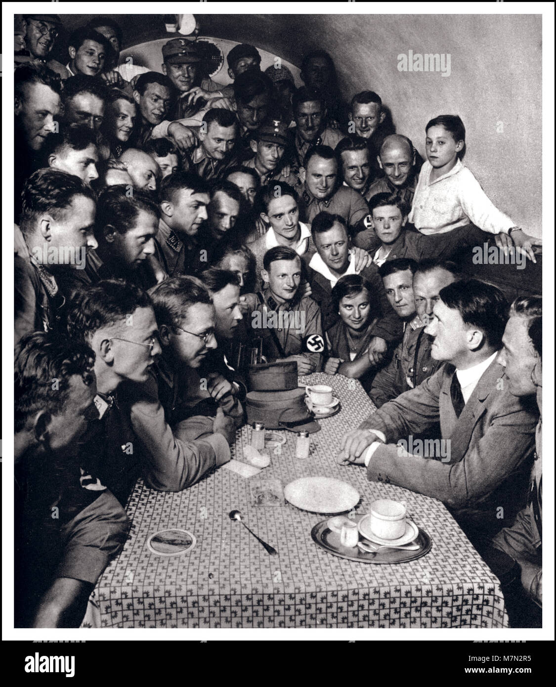 1933 Adolf Hitler posed propaganda image political meeting with SA men and other admirers in the basement casino - Stock Image