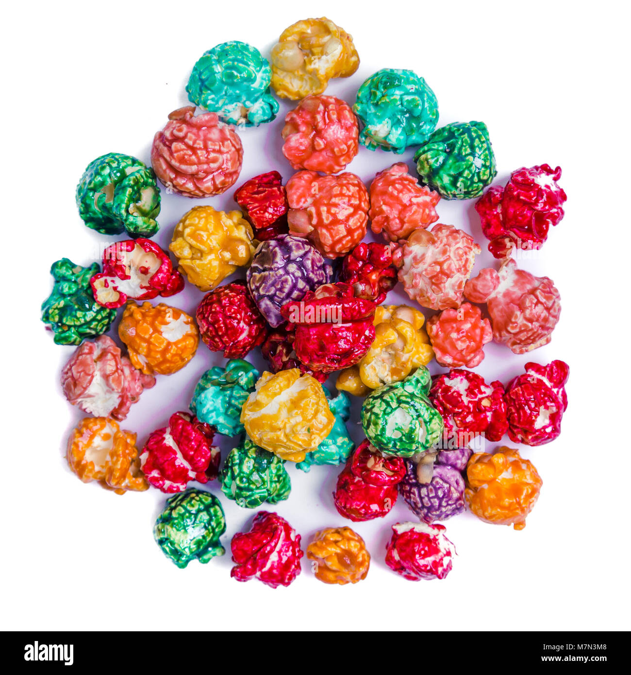 Brightly Colored Candied Popcorn, white background. Horizontal image of Junk food, fruit flavored popcorn in light - Stock Image