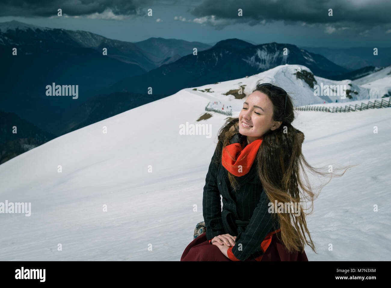Young woman sits on the top of snowy mountains in the ski resort. Trendy traveler enjoys wonderful day and takes - Stock Image