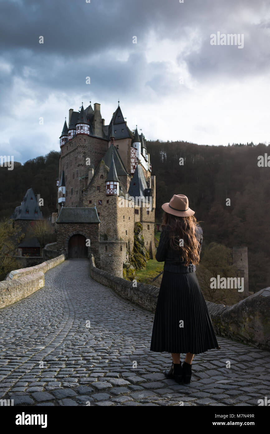 Young unrecognizable woman stands back on road leading to a beautiful castle. Fabulous medieval place. Trendy girl Stock Photo