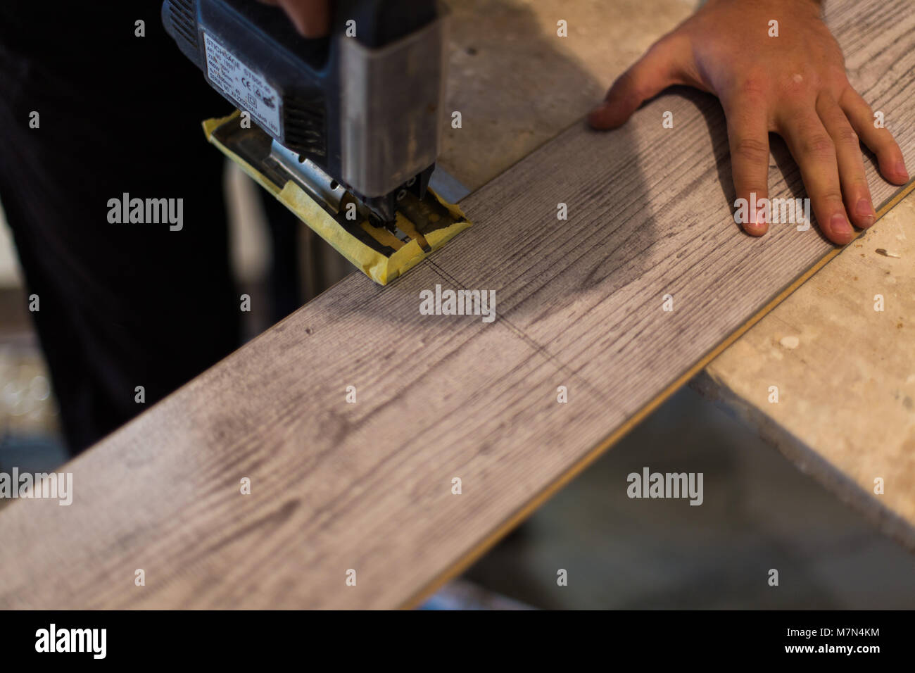 Contractor Cutting laminate flooring lengthwise. Workers Cutlaminate flooring with electric saw. - Stock Image