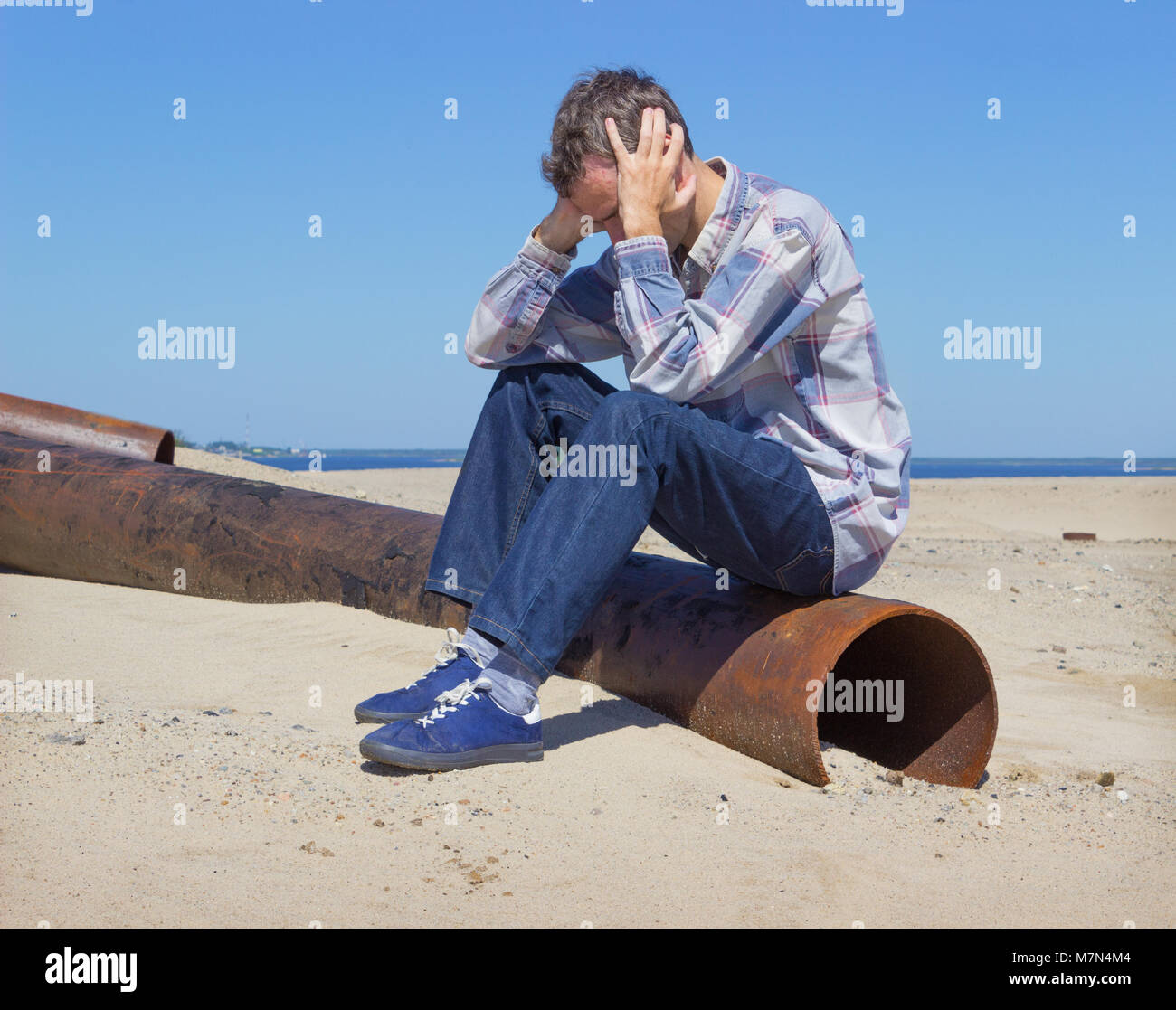Lonely young man, suffering from depression sitting on wasteland - Stock Image