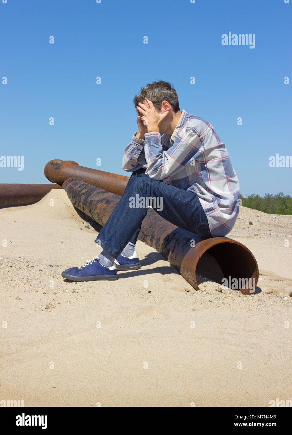 Lonely young man suffering from depression sitting on wasteland - Stock Image