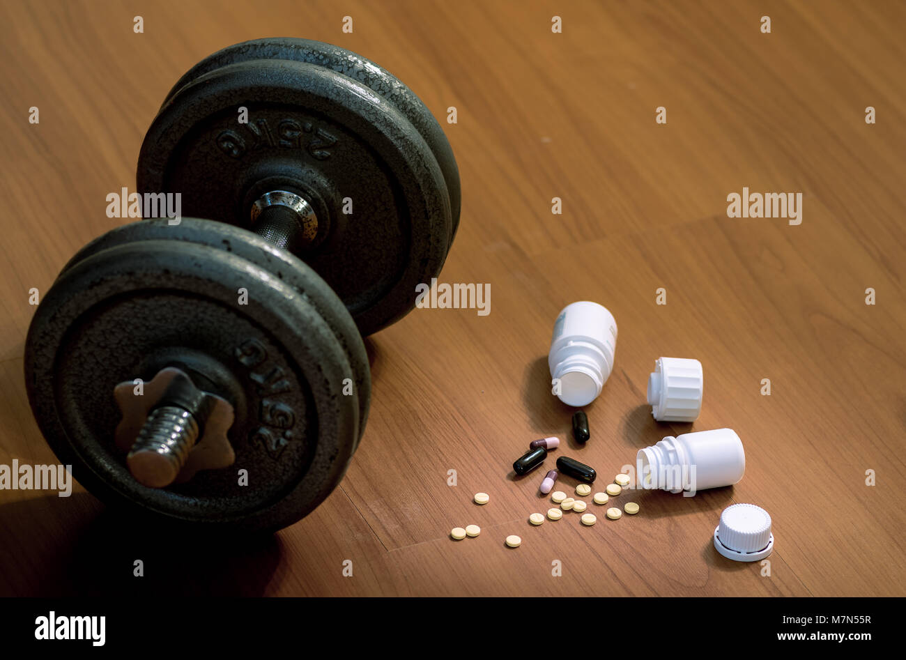 Steroid pills and capsules with dumbbell weight in the background - doping in sport. Stock Photo