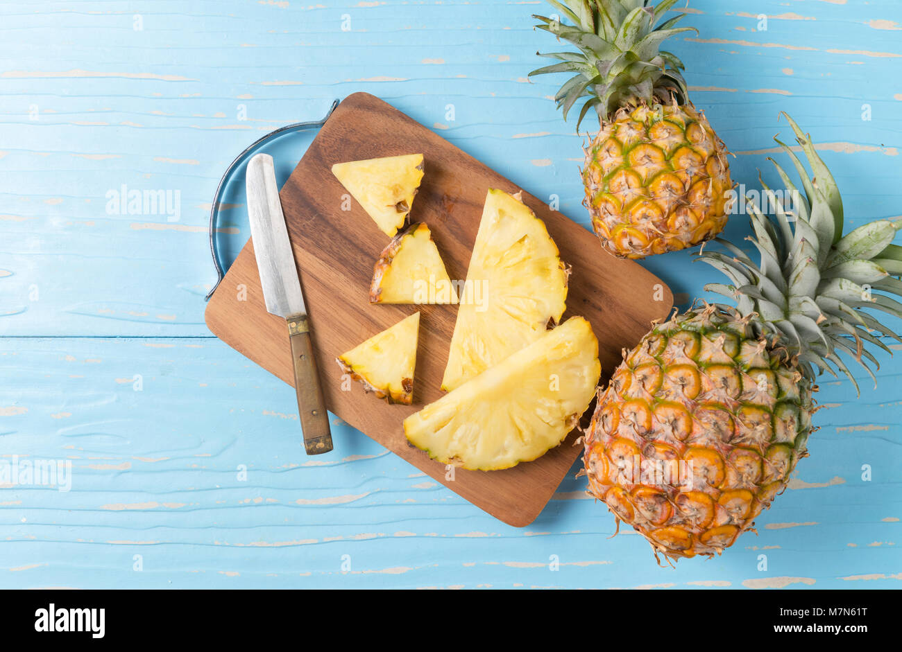 fresh sliced pineapple on wood block and blue wood background, summer fruits concept Stock Photo