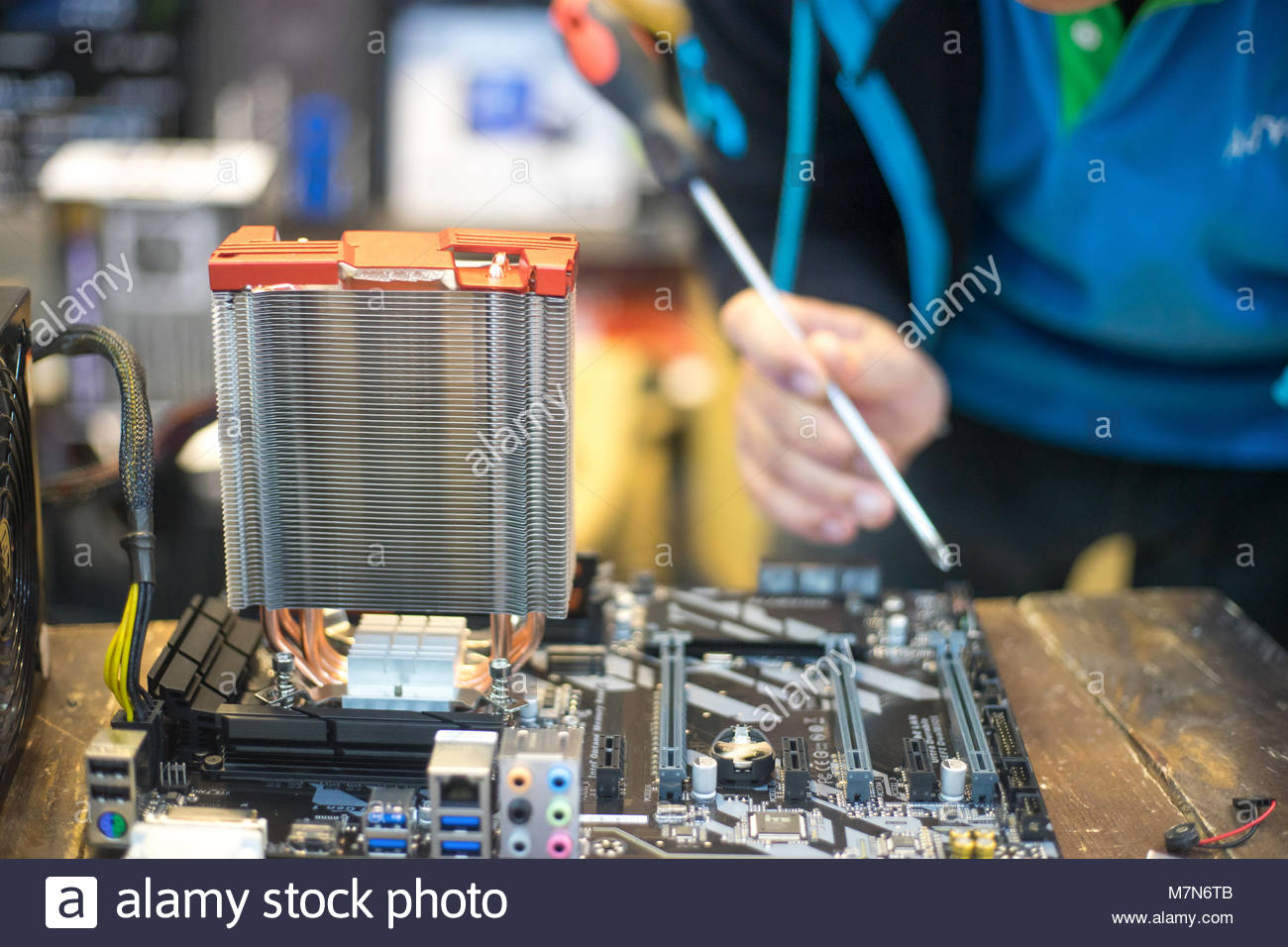The technician hold the screwdriver for repairing the computer. the concept of computer hardware, repairing, upgrade - Stock Image