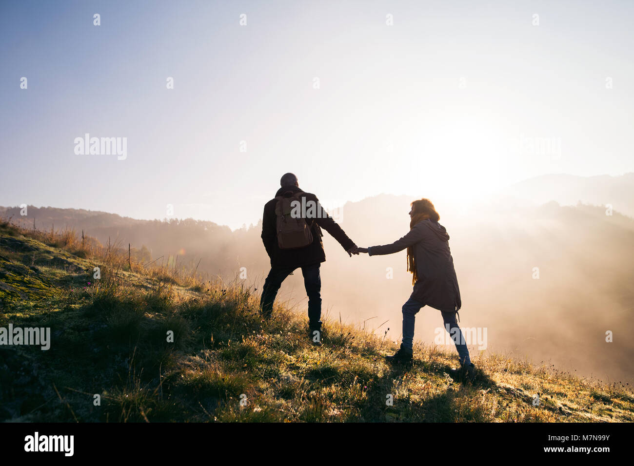 Senior couple on a walk in an autumn nature at sunrise. - Stock Image