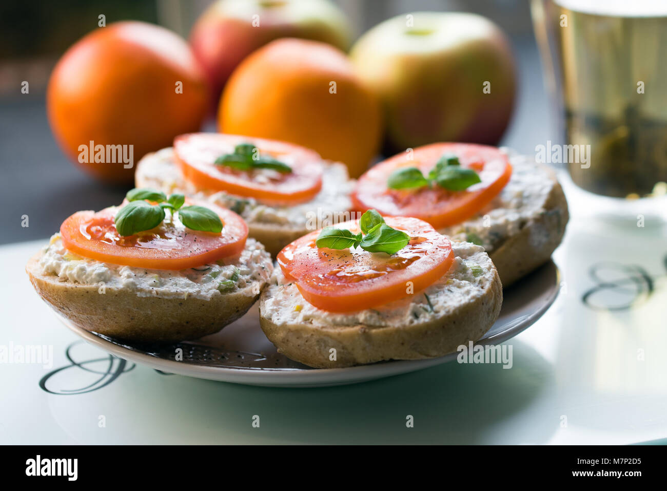 Sandwich with tomato on top and white chese at white plate in the glare of the morning sun - Stock Image