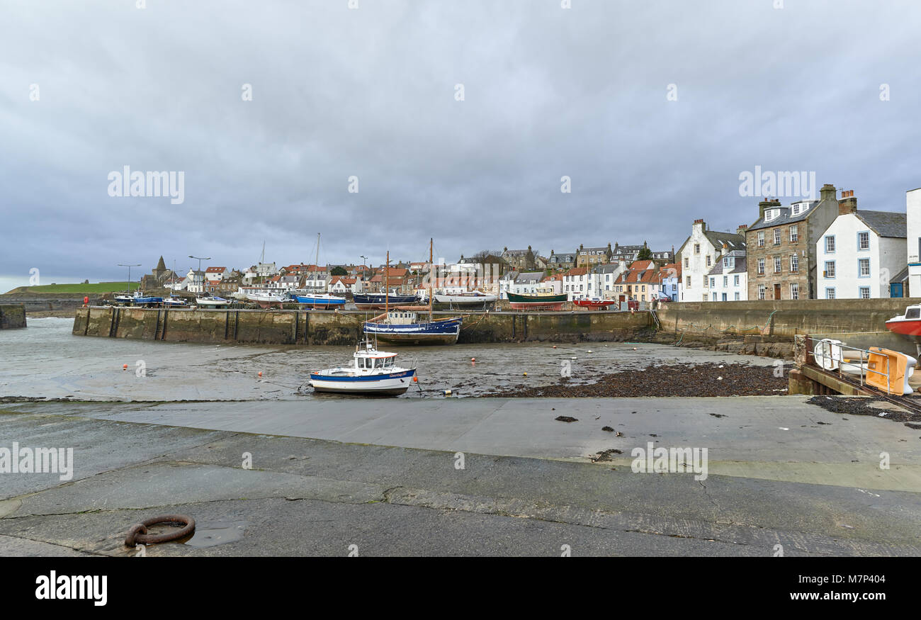 St Monans harbour on a Wet, Windy Winters day one January. The Old Fishing Boats aground on the Mud during the low Stock Photo