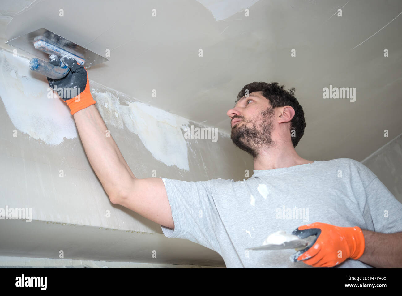 Worker Plastering Ceiling Stock Photo