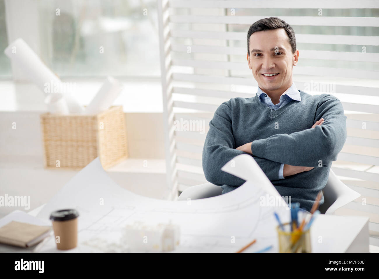 Happy young man working in his office - Stock Image