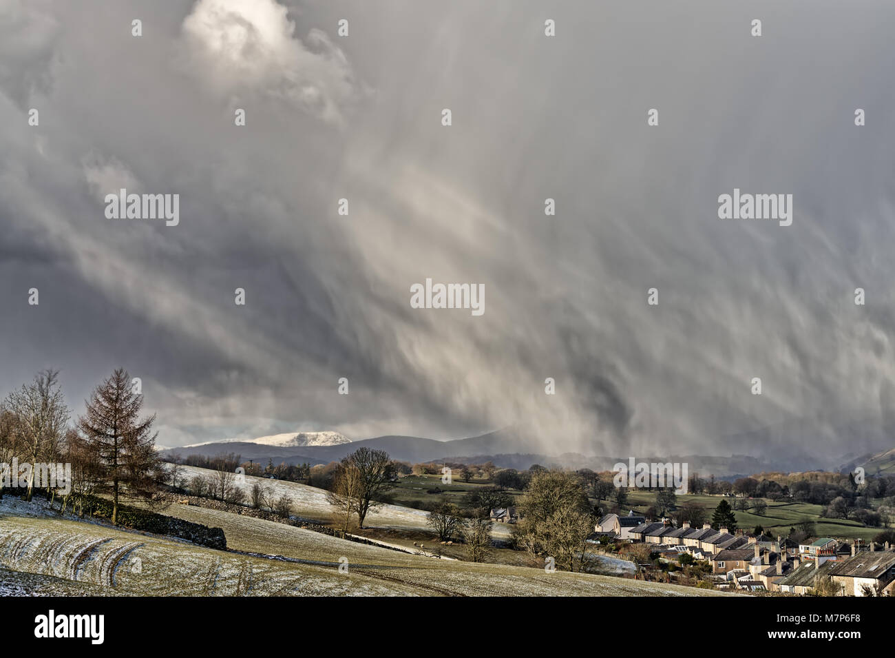 A snow shower falling in the North of England with a hilly backd - Stock Image