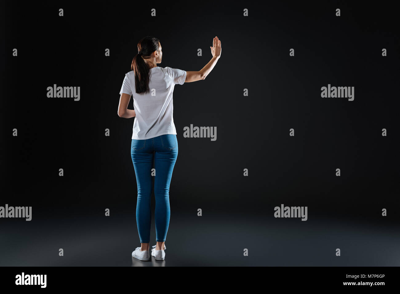 Slim pretty girl standing and holding had up. - Stock Image