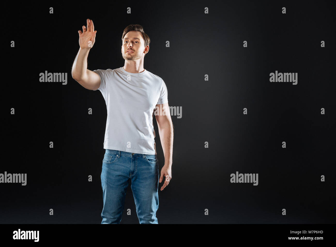Handsome stylish man lifting hand and looking aside. - Stock Image