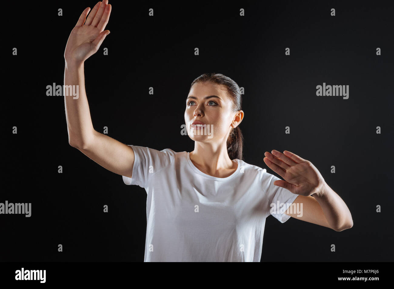 Funny cute woman lifting hands and looking up. - Stock Image