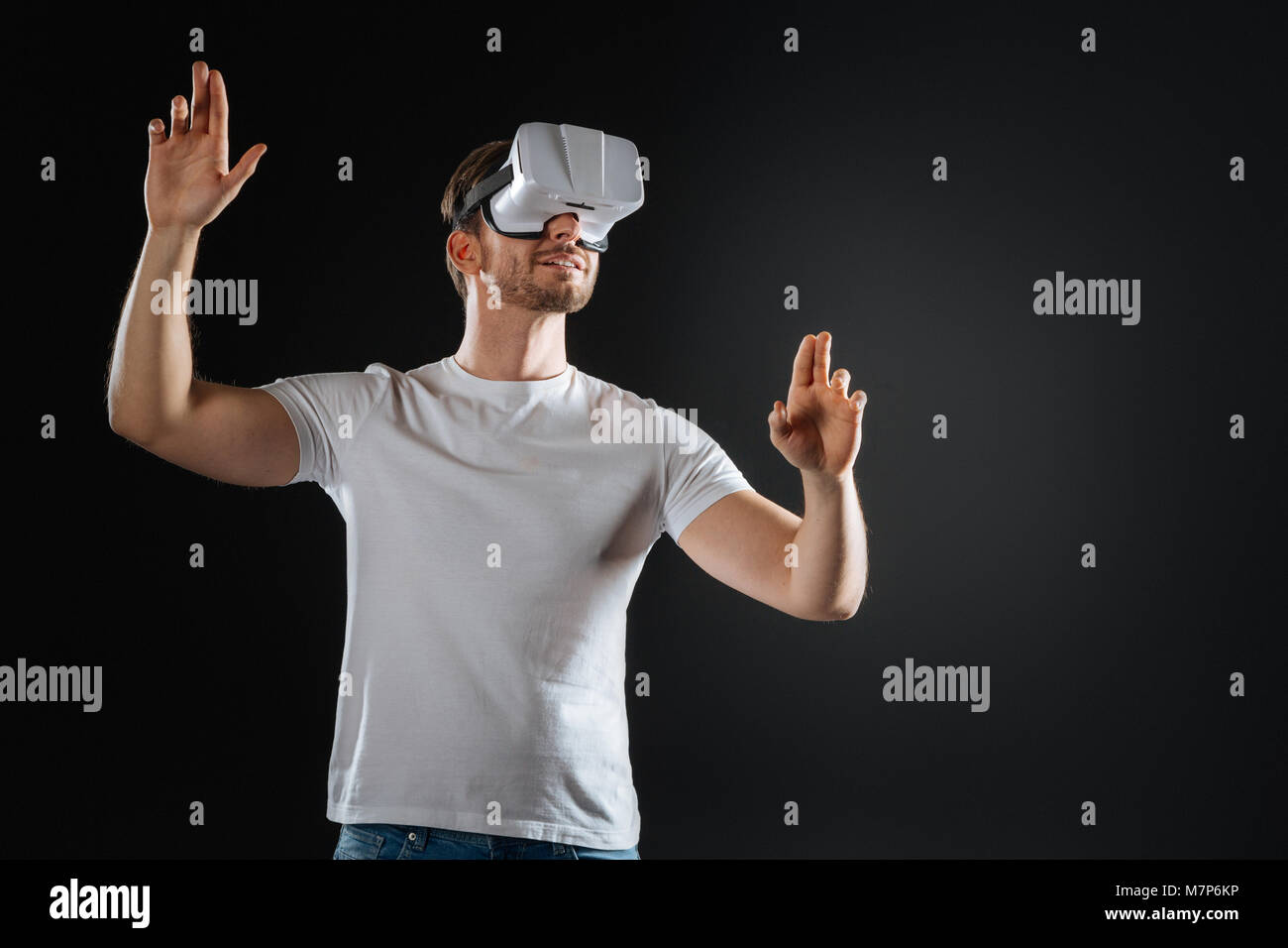 Stylish occupied man smiling and examining VR glasses. - Stock Image