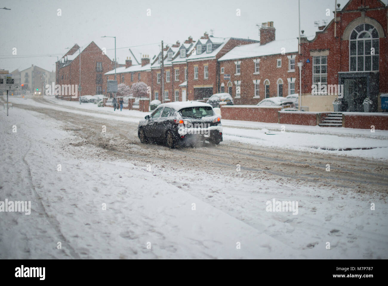 traffic chaos in snow and blizzard conditions as cars skid in street with row of houses in background UK - Stock Image