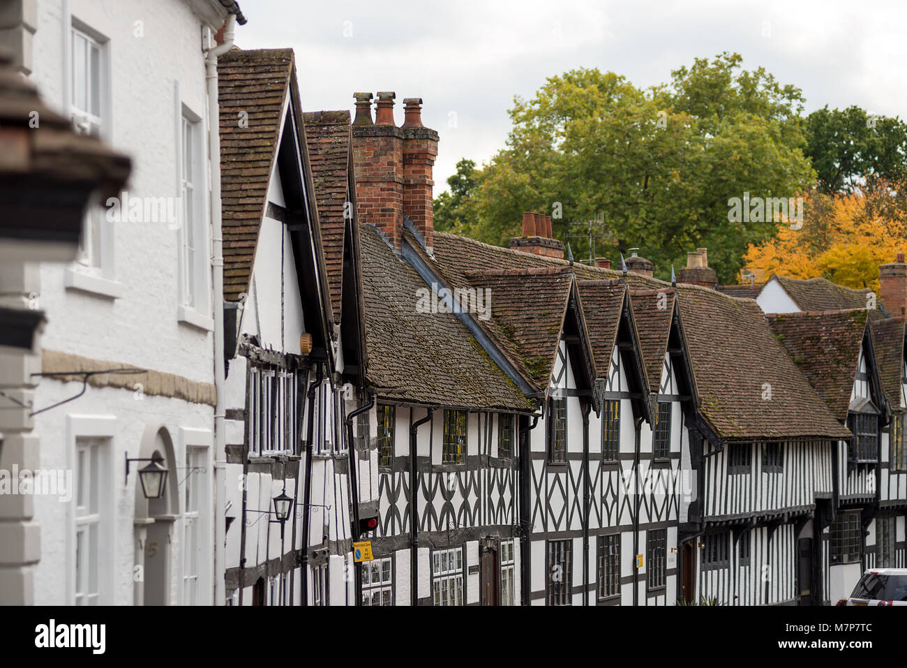 A view along the curved street of Mill Street, Warwick of 16th / 17th century era Tudor style houses with tiled - Stock Image