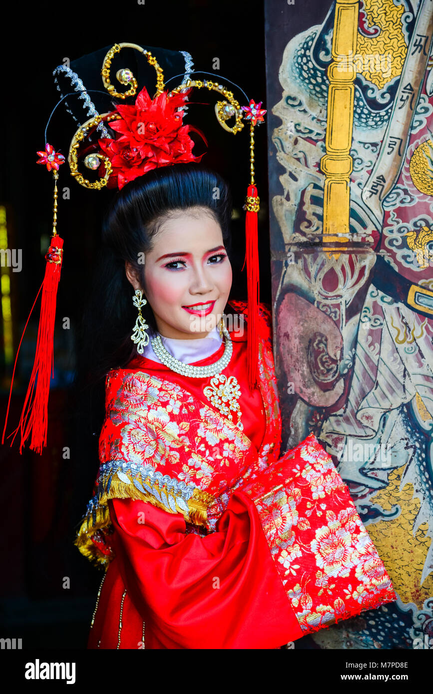 Chachoengsao, Thailand - July 14, 2013 : Beautiful woman with traditional chinese red dress at Chinese shrine door - Stock Image