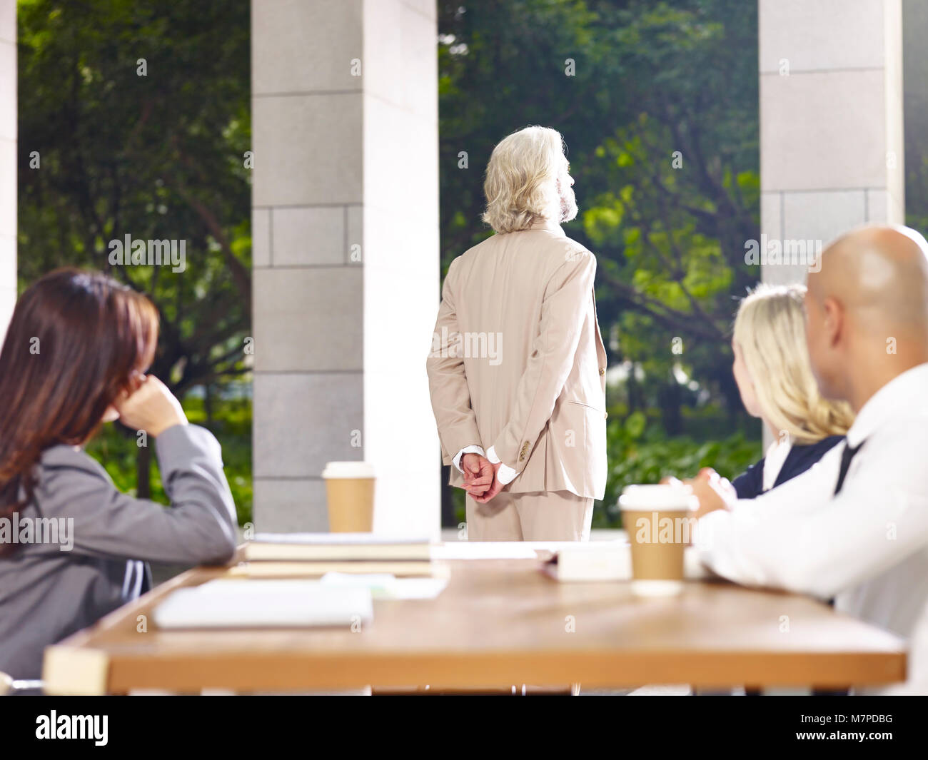 caucasian corporate business leader standing thinking during meeting, hands behind back, rear view. - Stock Image