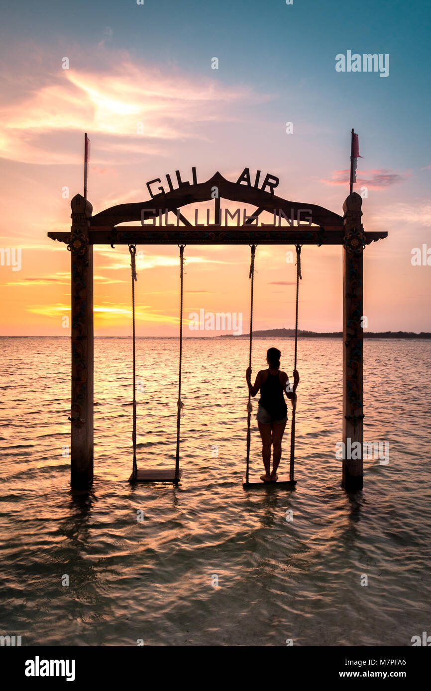 The beautiful beach side swings of Indonesia look even more amazing during the sunset - Stock Image