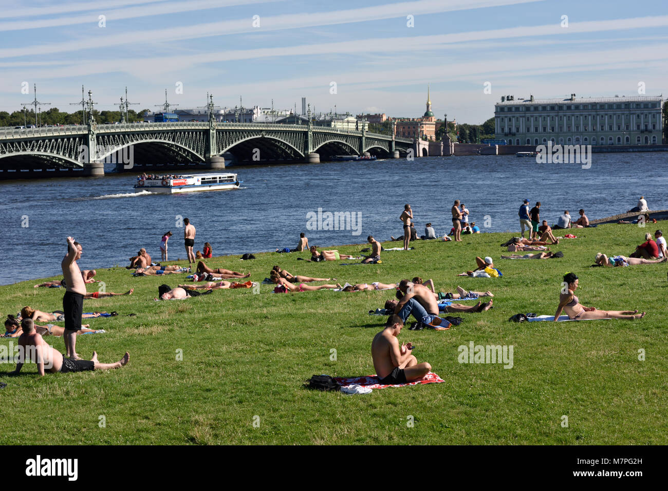 St. Petersburg, Russia - August 7, 2015: People resting on the beach of Zayachiy island. Meteorologists say that - Stock Image