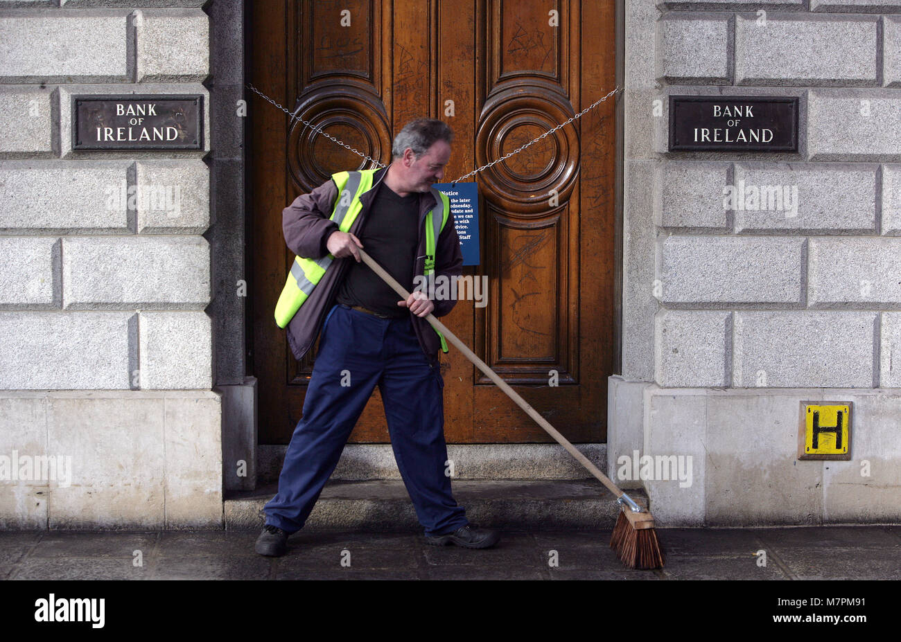 A workman cleans up outside the Bank Of Ireland Headquarters in Dublin, Ireland, 1 Oct, 2008. The Irish government - Stock Image