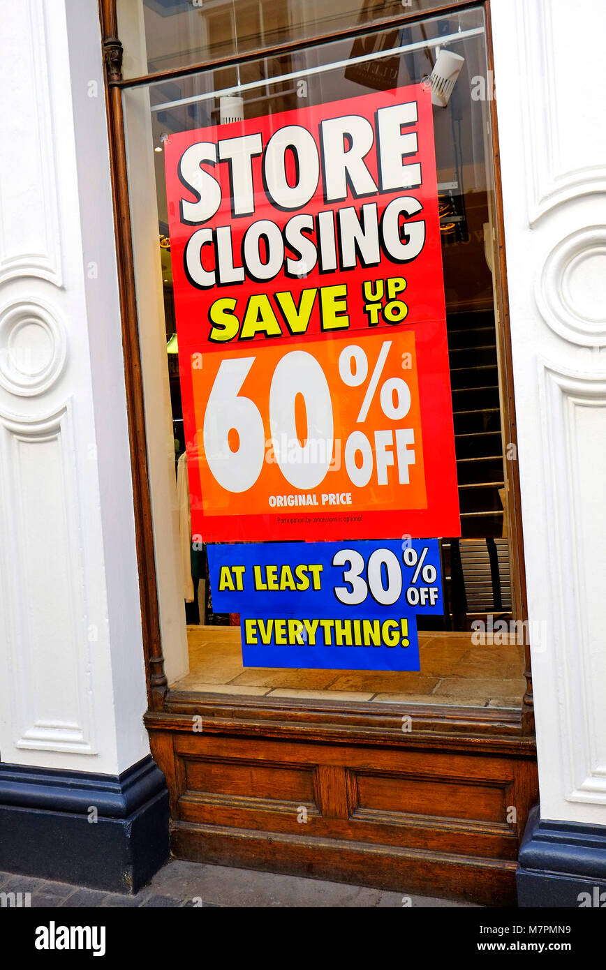 store closing down sale poster in shop window - Stock Image