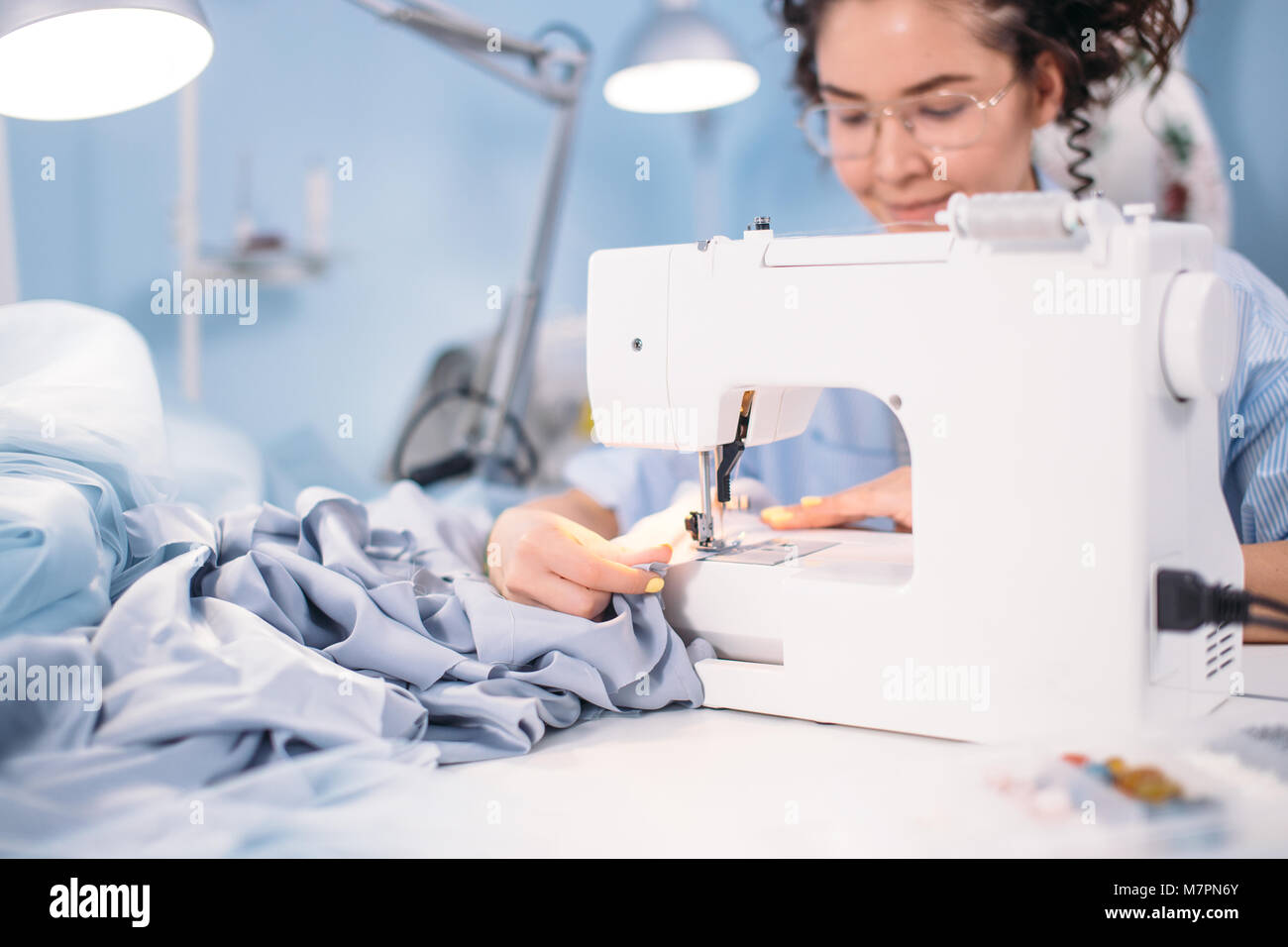 cropped shot of woman learning to sew on sewing machine in design studio. attending lessons of sewing. hobby. free - Stock Image