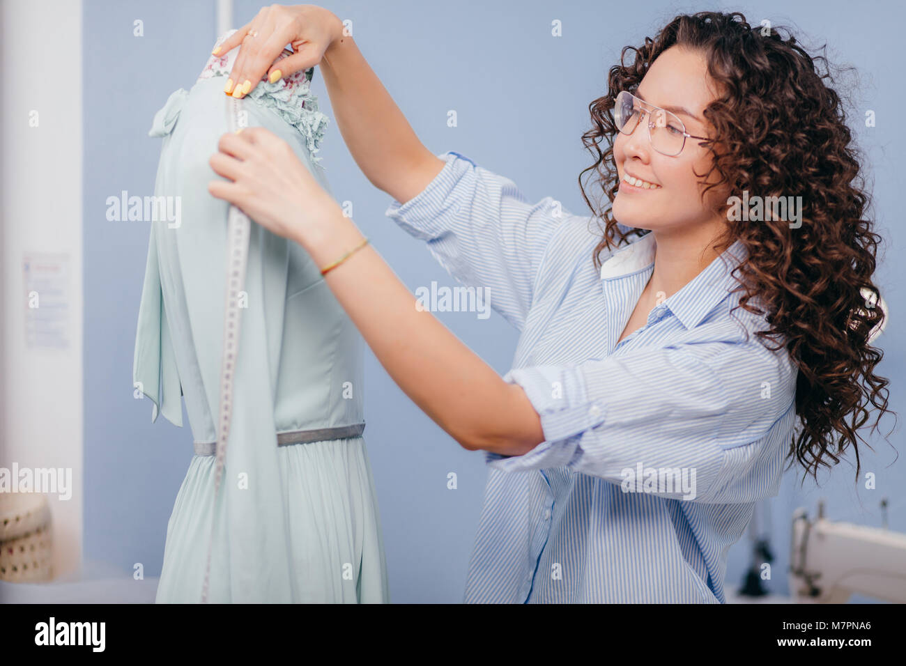 Woman tailor working with dummyin room. measuring shoulder with flexible ruler - Stock Image