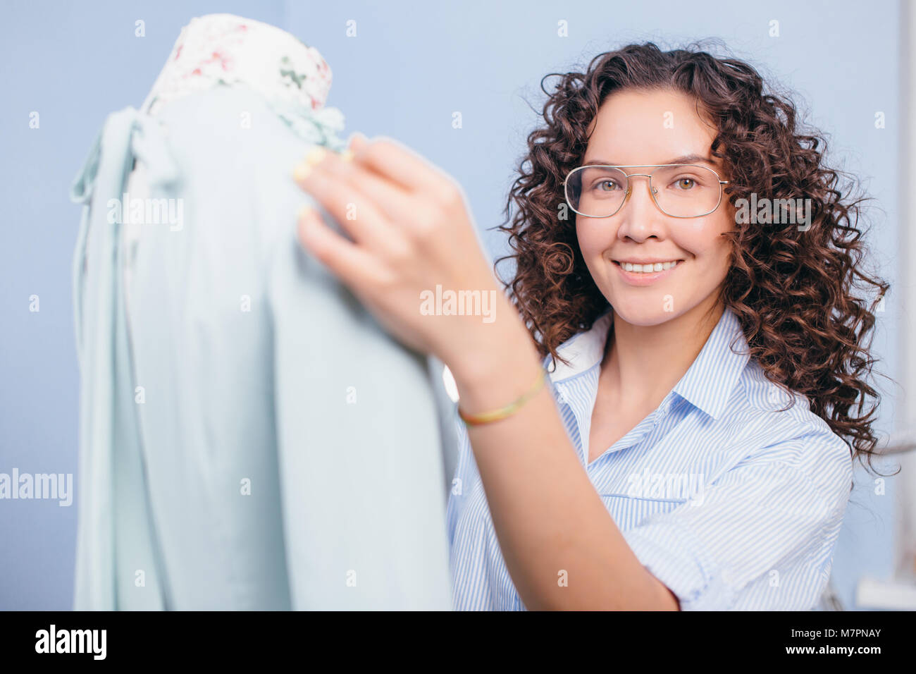 close up shot of seamstress adjusting dress on dummy at tailor shop. tailor service. making clothers. - Stock Image