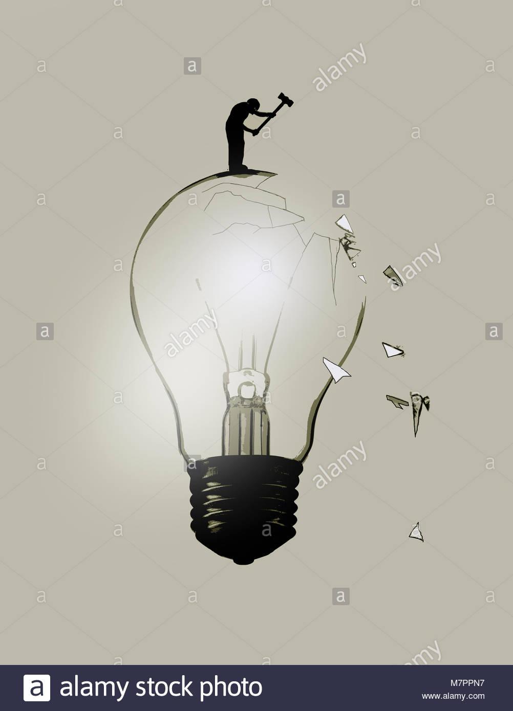 Man breaking light bulb with sledgehammer - Stock Image