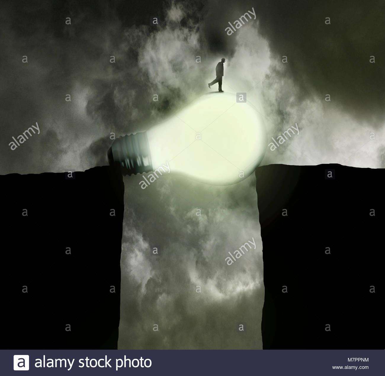 Businessman bridging the gap with illuminated light bulb - Stock Image