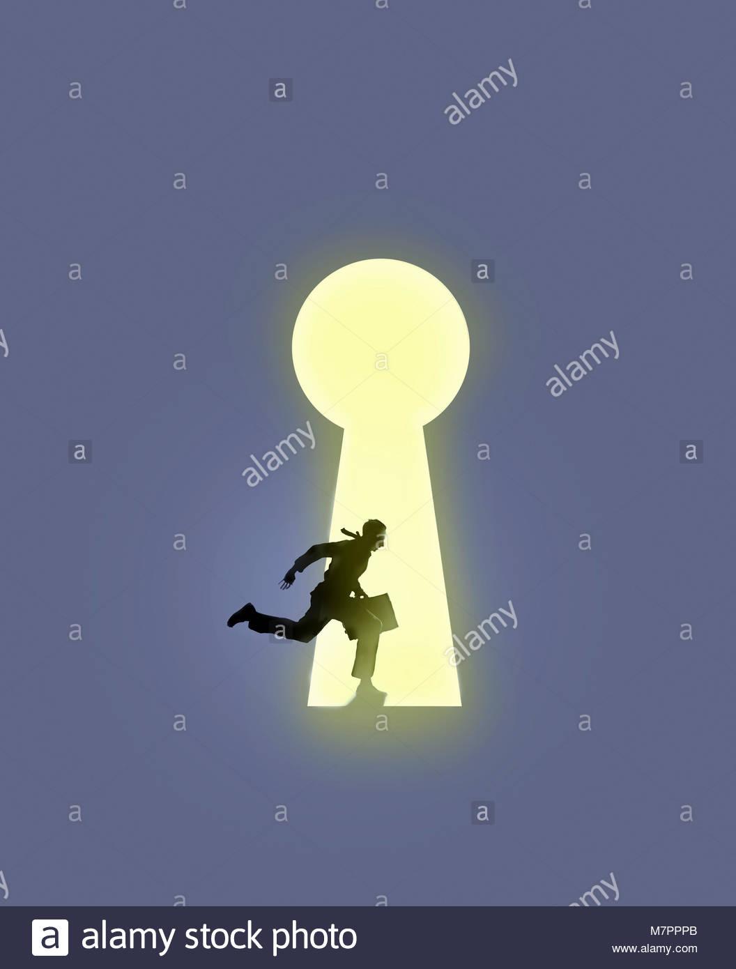 Businessman running into large illuminated keyhole - Stock Image