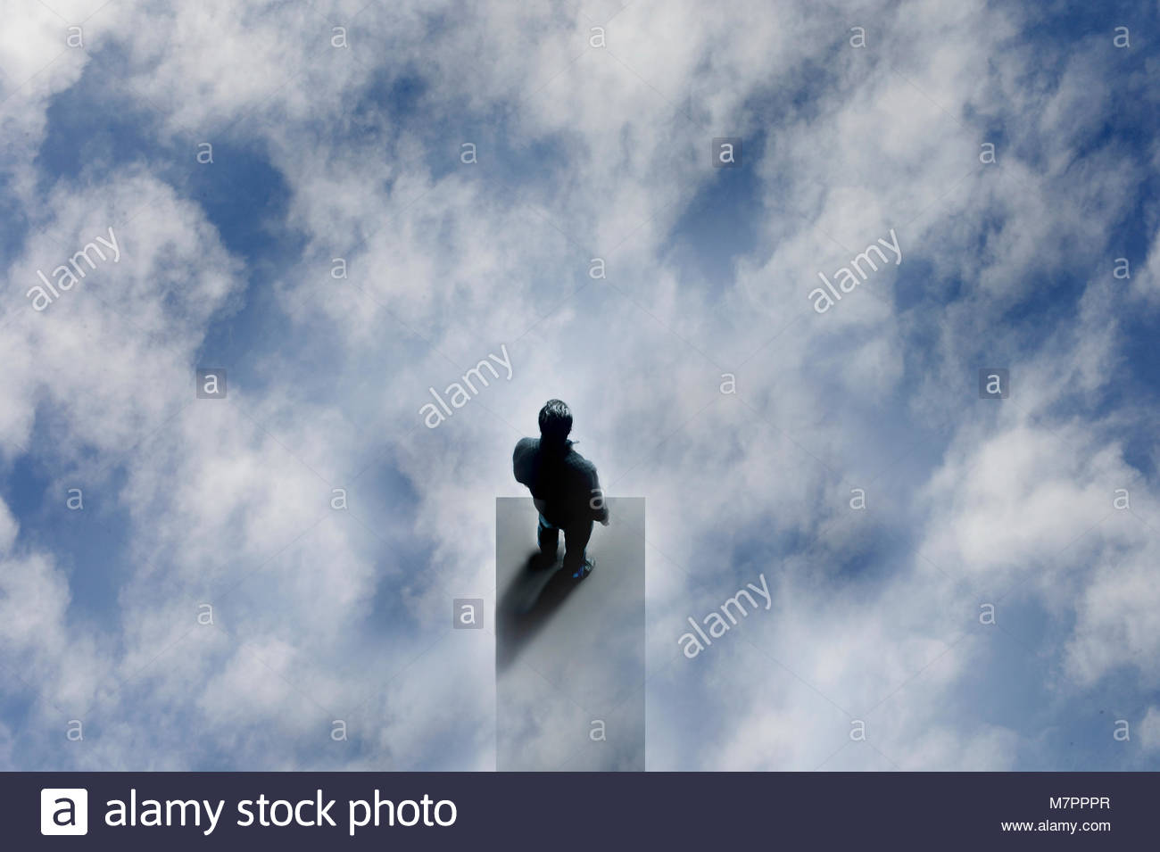 Overhead view of man at the edge of diving board in the sky - Stock Image