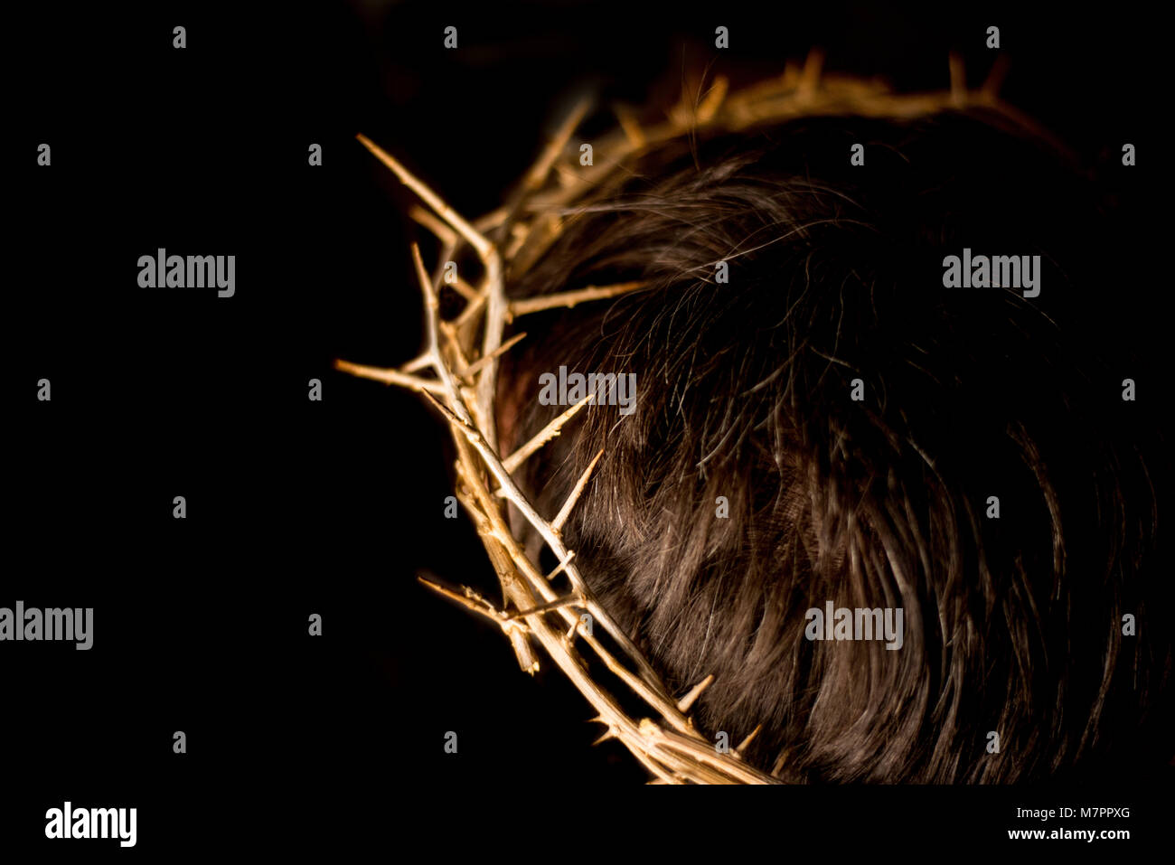 A crown of thorns on a head to represent Jesus Christ and Christianity. - Stock Image