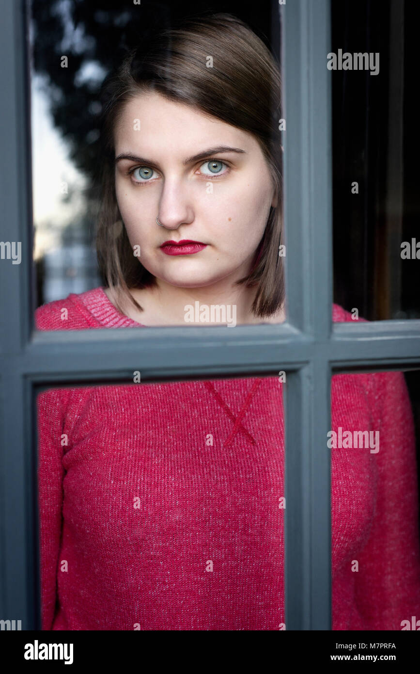 A teenaged girl looking out a window. - Stock Image