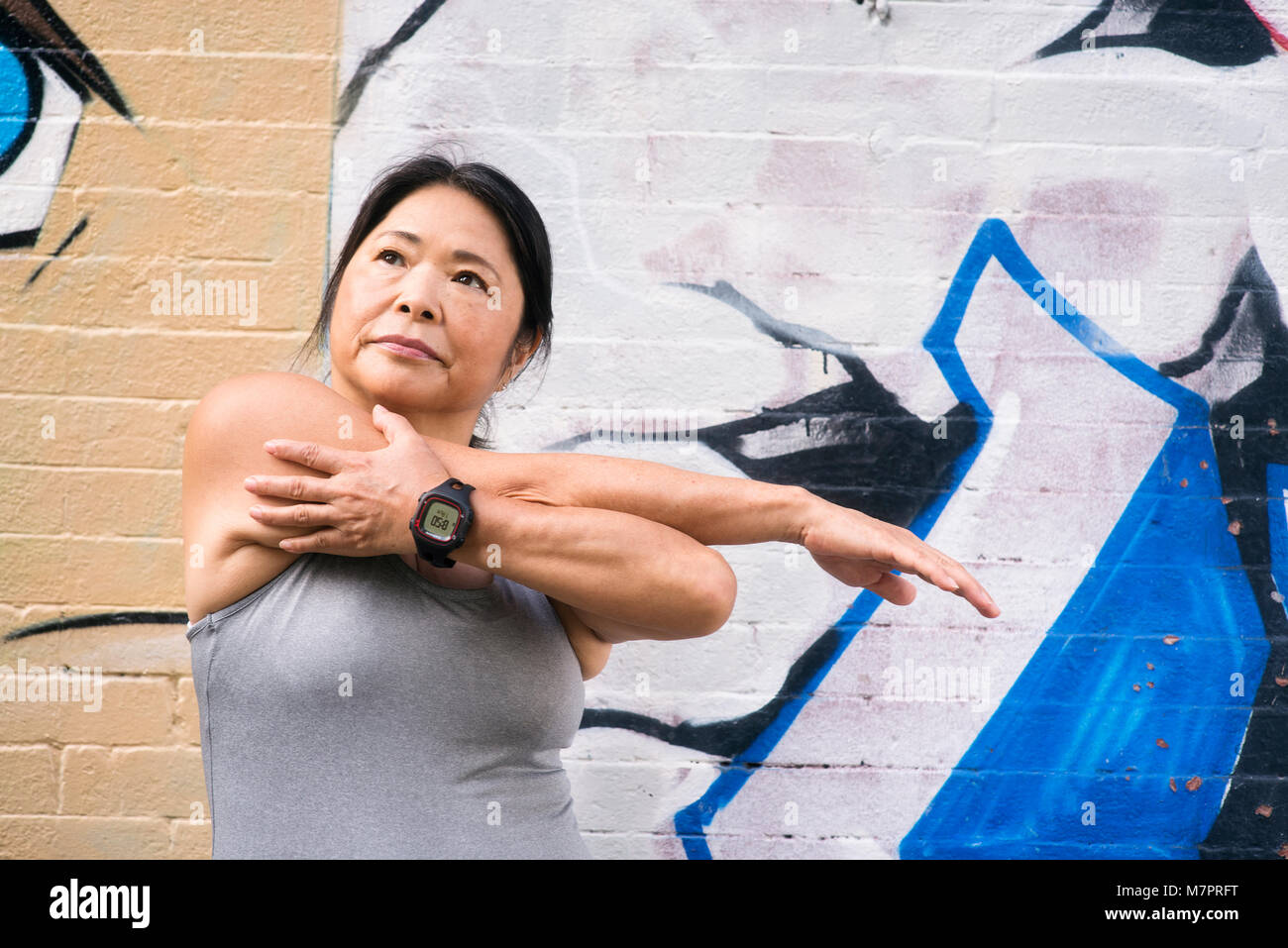 A woman (65) wearing a fitness device stretching out in preparation for a workout. - Stock Image