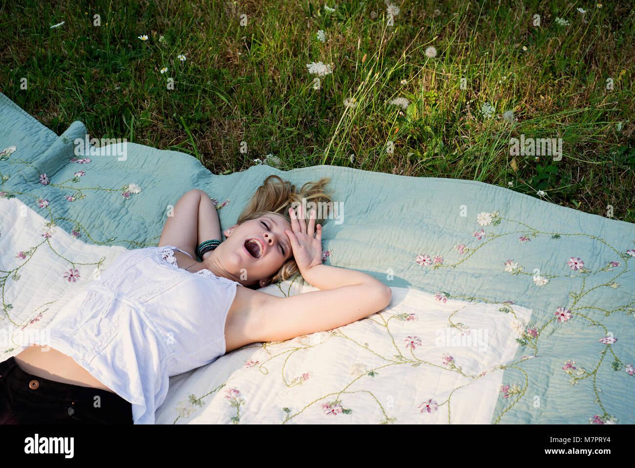 Teenaged girl yawning in the grass - Stock Image