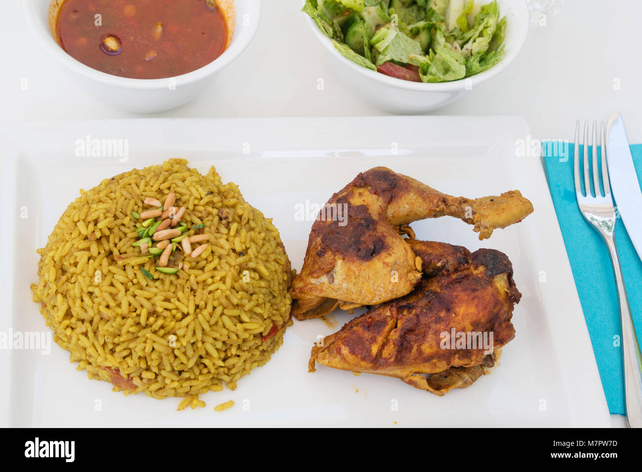 Fried chicken legs with rice accompanied with vegetable salad - Stock Image