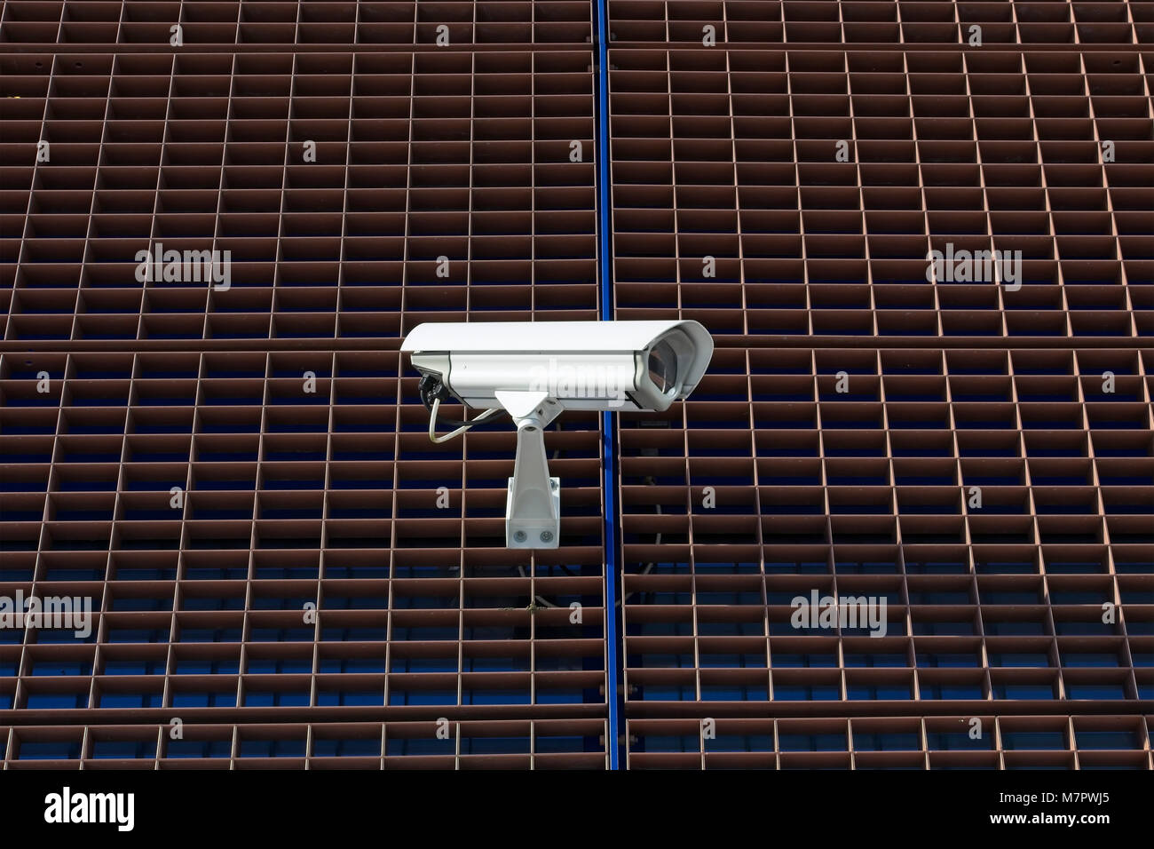 Surveillance camera on building exterior wall - Stock Image