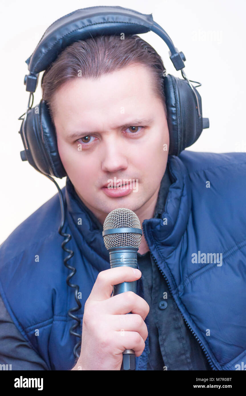 Portrait of young Caucasian Ethnicity man commentator with microphone and headphones on white background - Stock Image