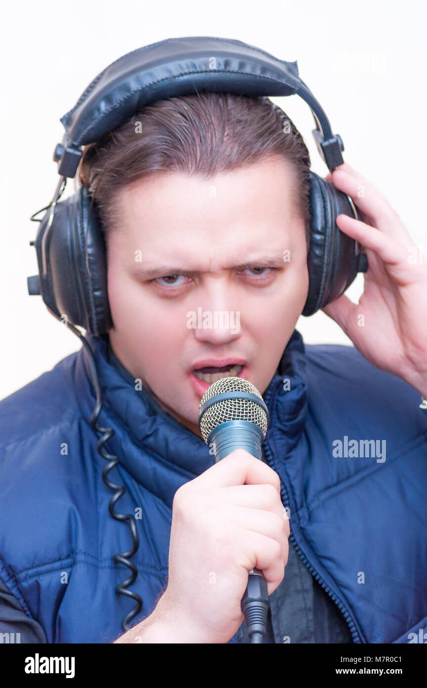 Portrait of young Caucasian Ethnicity emotional man commentator with microphone and headphones on white background - Stock Image