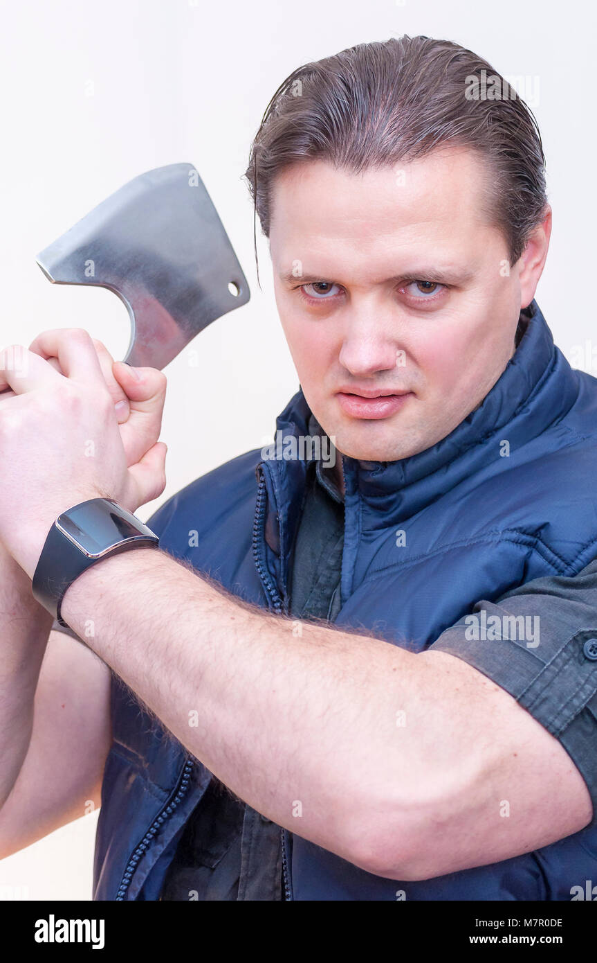 Portrait of young Caucasian Ethnicity man threatening with cleaver kitchen ax on white background - Stock Image