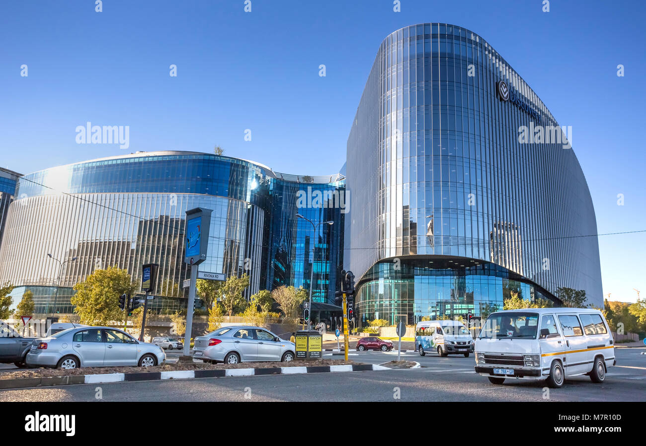 Johannesburg, South Africa - March 8, 2018: Glass fronted modern building with road with cars in foreground. - Stock Image