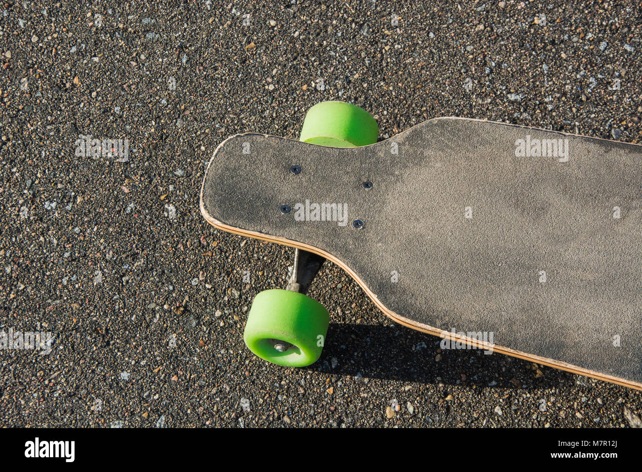 a3242e0187 Old used longboard isolated on the ground. Black skateboard on an empty  asphalt road. Close up.