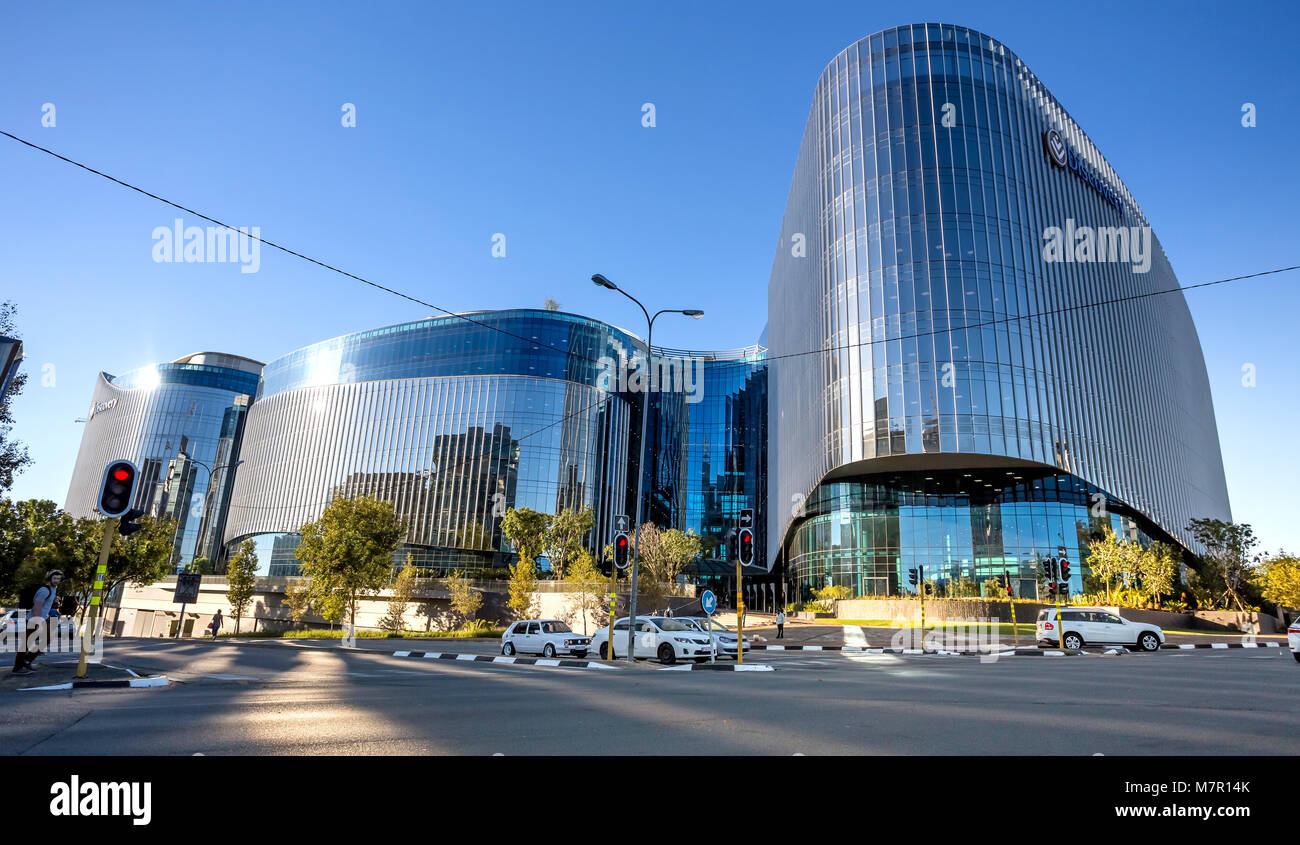 Johannesburg, South Africa - March 8, 2018: Glass fronted modern building with road in foreground. light reflection - Stock Image