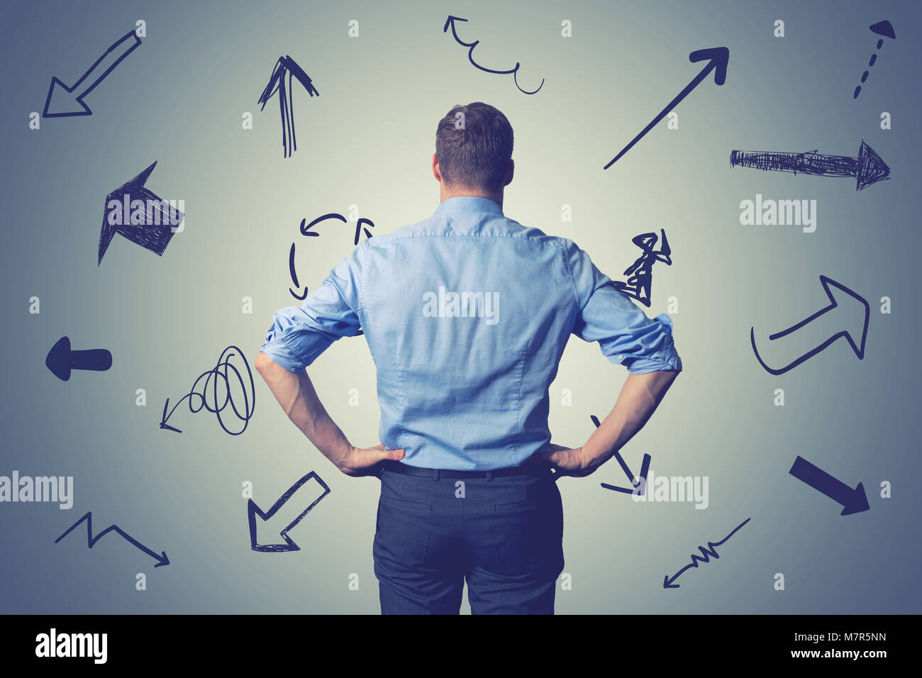 confused businessman with direction arrows. choosing the right way decision concept - Stock Image